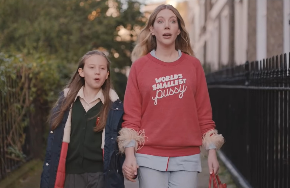 Katherine and her daughter walk down a residential street holding hands. Her daughter has her school uniform on, while Katherine is wearing a red jumper with fluffy pink cuffs and 'world's smallest pussy' embroidered on.