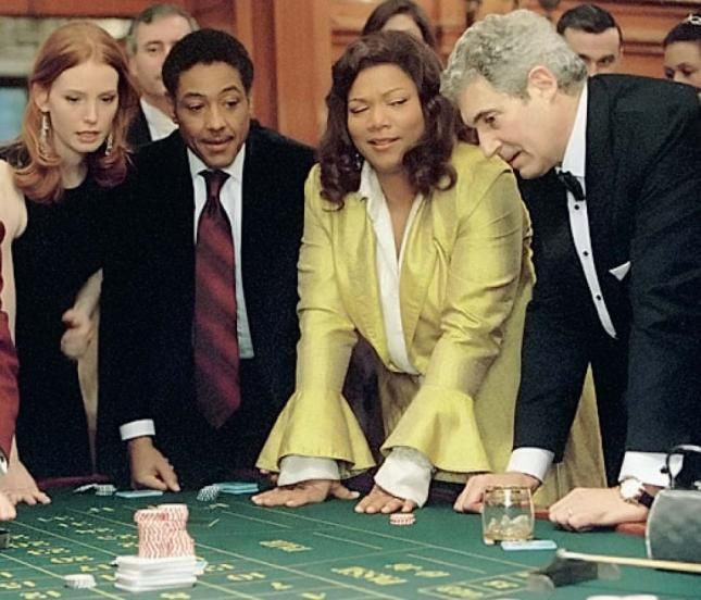 Four people (including Queen Latifa) stand round a casino table, Queen Latifa is giving her neighbour the side-eye