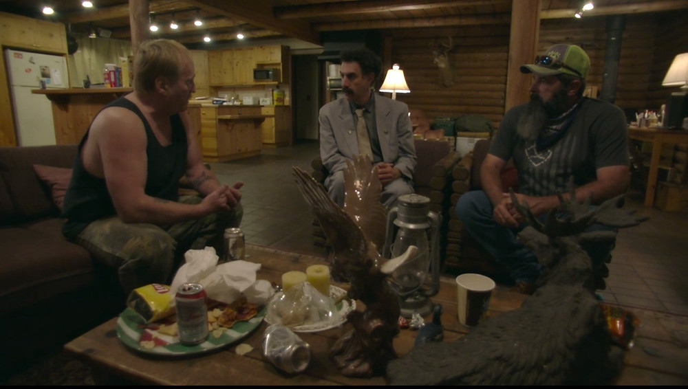 Borat sits with two men in a log cabin, they are intently discussing something. Beer cans are strewn across the table.
