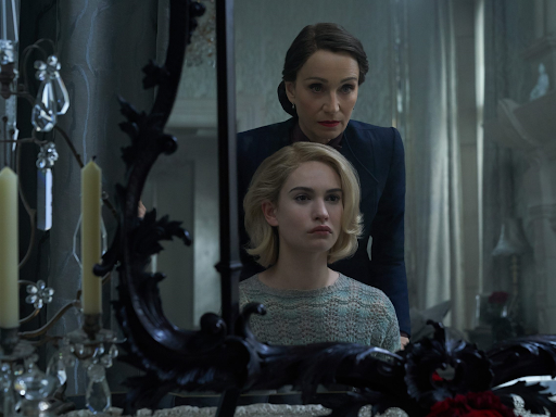 A frame from Wheatley's Rebecca: Mrs de Winter (Lily James) looks into the mirror with Mrs Danvers standing behind her. The mirror is framed with ornate gothic designs and candlesticks.