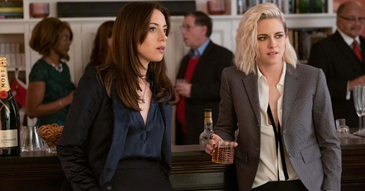 Kristen Stewart and Aubrey Plaza in Happiest Season stand in a crowded bar wearing power suits, looking somewhere in the distance.