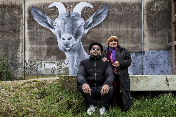 A still from Visages, Villages: Varda and JR post in front of a large graffittied wall, upon which they've just posted a large mural of a goat with horns