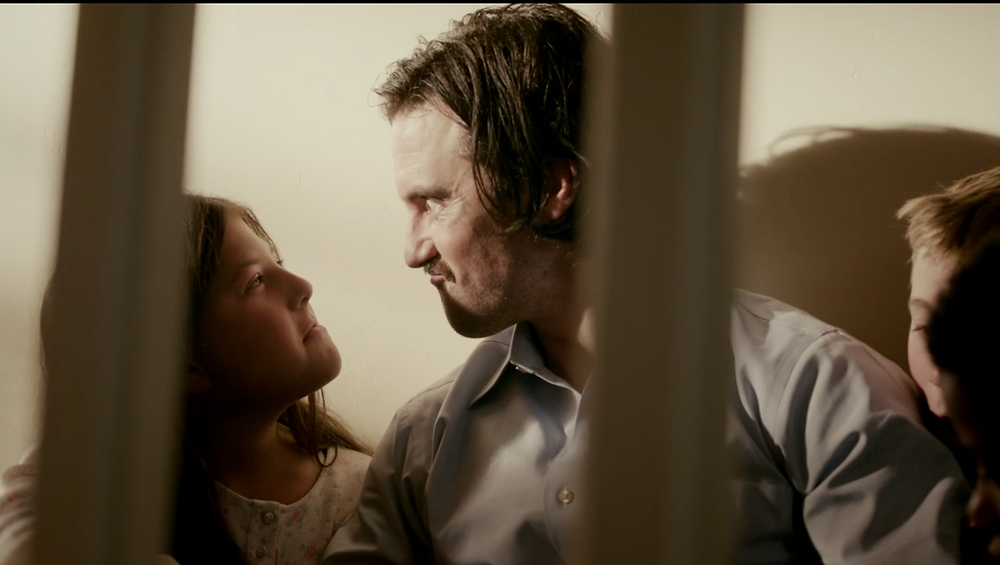 A still from This Is Us, Jack and his daughter (a child) pull silly faces at each other.
