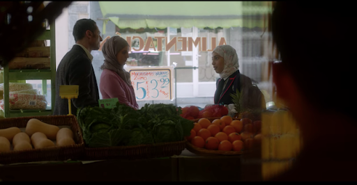 A still from Netflixs Elite: Nadia and her parents stand outside a fruit and veg stand facing each other. Someone is watching them from afar, but we only see the back of their head.
