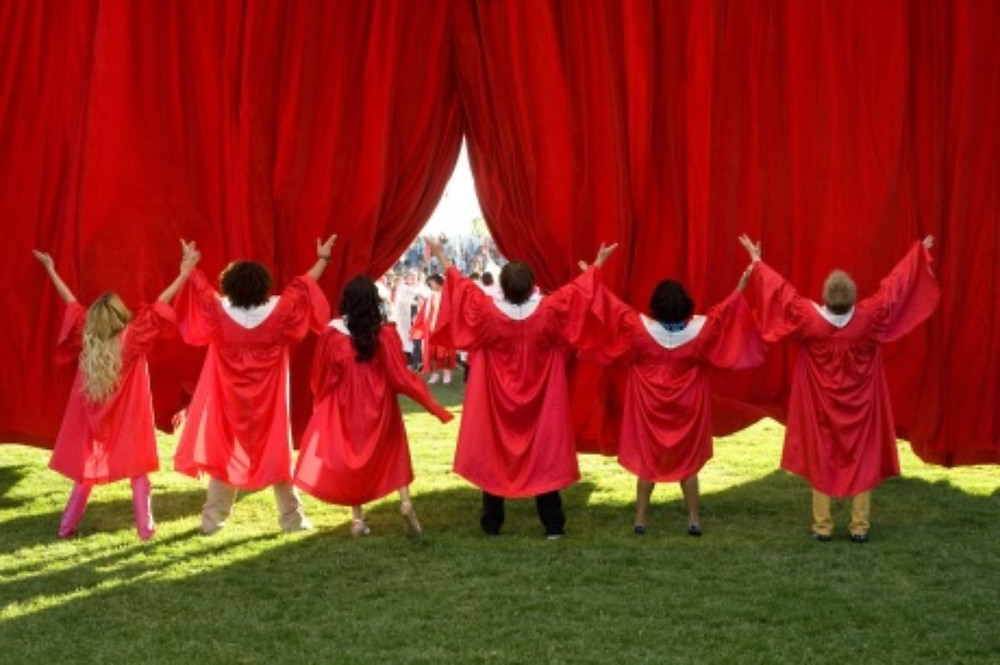 The HSM crew standing in front of a red curtain opening, their arms in the air mid-dance and wearing red graduation robes.