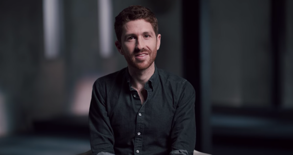 Tristan Harris sits in a dark room, smiling at the camera