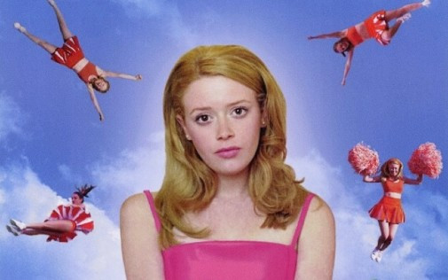 A still from But I'm a Cheerleader, a girl with blonde hair and a pink dress sits looking at the camera, with the blue sky behind her and cheerleaders in various poses around her head