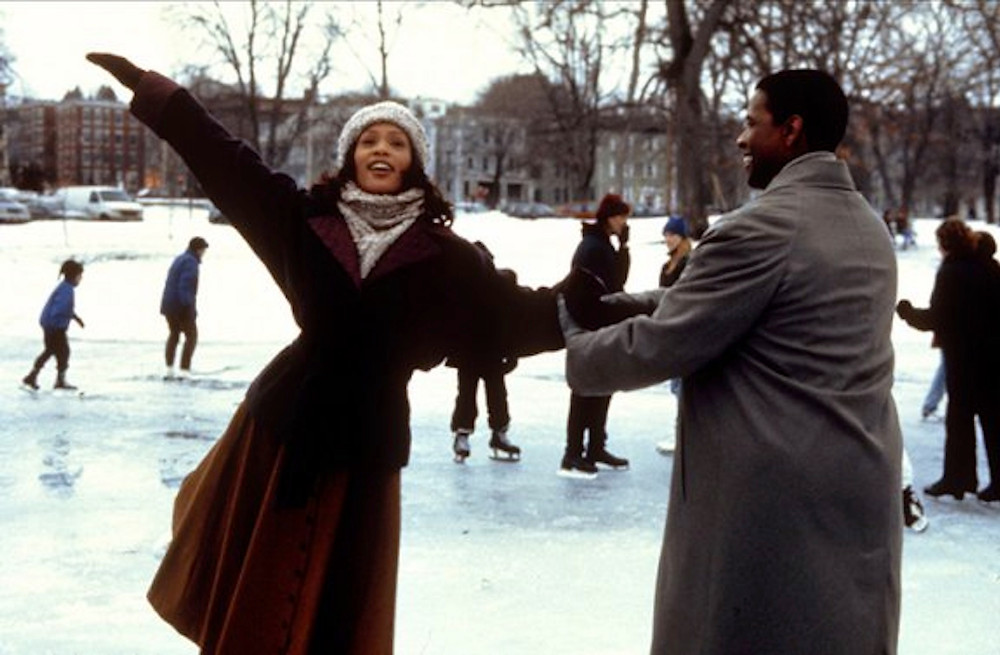 Whitney Houston as Julia and Denzel Washington as Angel Dudley ice skate on a frozen pond, Angel Dudley is holding Julia's arm while she dances with her arms elegantly in the air