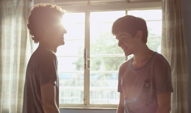 A still from The Way He Looks, two young men are stood in front of a window, all we see are their silhouettes. They are laughing and smiling at each other.