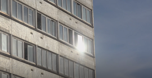 A plain block of flats against a blue sky, the sunlight is glinting off the windows