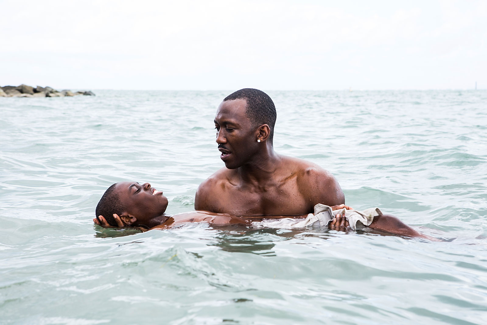 A still from Moonlight, two Black men in the sea, Blue holds the young Chiron's head up in the water, the sea is calm and the moment is tranquil.