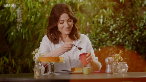 Sitting in a garden, Nigella Lawson smiles at her honey spoon while she drizzles it on a cake.