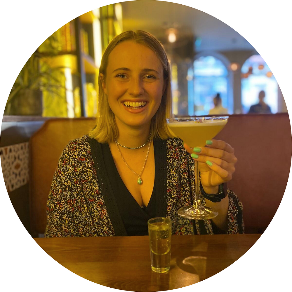 An image of Ellie Paine, holding a cocktail and smiling