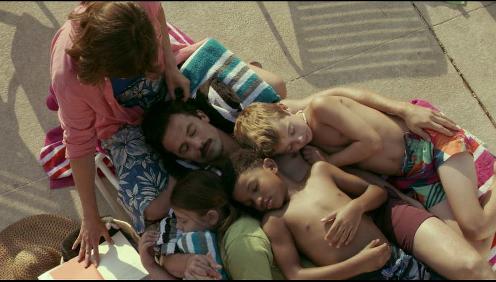A still from This Is Us: A shot from above, the family is huddled up in the sun, the children hugging their Dad, his head in the Mum's lap