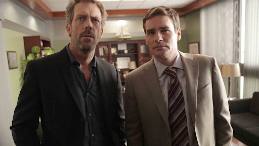 Dr. House and Dr. Wilson in House are stood next to each other in an office, looking just above the camera at something with faces of concentration