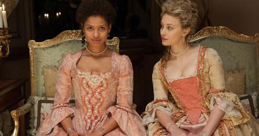 A still from Belle: Dido and Elizabeth sit in opulent historical costume on ornate chairs looking forwards. Elizabeth is leaning towards Dido and looking at her.