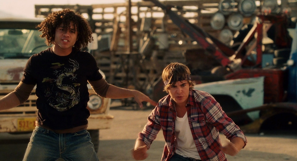 Troy and Chad are in a junkyard, pulling what seems to be 'threatening' dance moves.