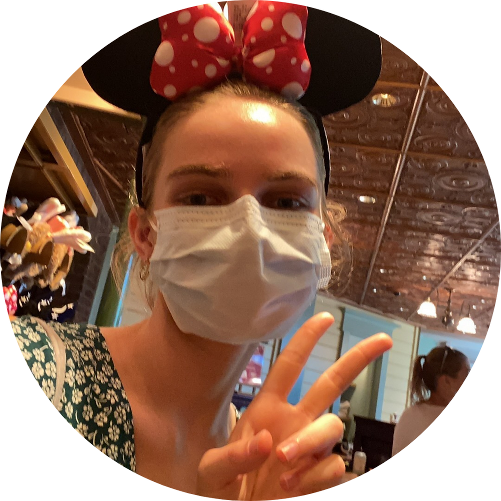 A profile picture of Claudia, she is wearing a surgical mask and Minnie Mouse ears and holding up a peace sign
