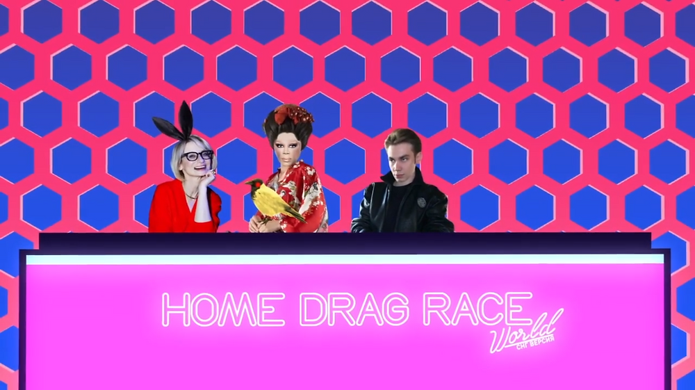 An animated version of the Drag Race judges, with three animated characters sat behind a garishly pink desk and background. The middle character is an animated version of RuPaul.