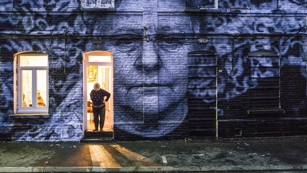 A still from Visages, Villages: an elderly woman stands in her doorway with her hands on her hips looking out. An image of her face is plastered across the entire facade of her house.