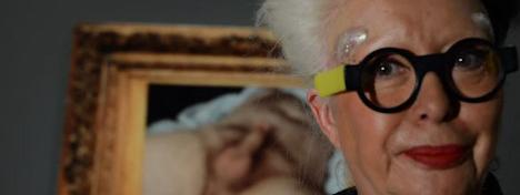 Orlan, with statement black and yellow glasses stands in the foreground, only her face is framed. In the background is an elaborately framed painting of a naked man lying on his back with an erection.