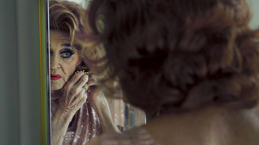 A still from PS Burn This Letter Please: an elderly drag queen puts on sparkly earrings in a mirror, the camera looking over her shoulder.