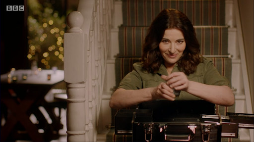Nigella Lawson sits on the stairs holding an old-fashioned suitcase in her lap and an obscured object in her hands, she smiles alluringly at the camera.