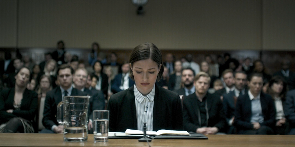 Black Mirror: A lone woman is sat at a desk in front of a crowd of people in suits. She is staring down at an open folder.