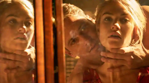 Mr and Mrs de Winter, (Armie Hammer and Lily James) look at themselves in a mirror, he is holding her neck in a sensual fashion. They are reflected twice in the frame by the mirror.