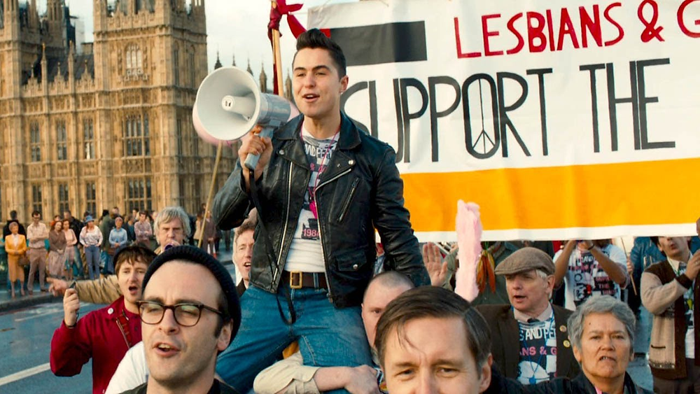 A still from Pride: a man in a black leather biker jacket sits on the shoulders of his friends with a megaphone. The protest is walking along London Bridge in front of the Houses of Parliament.