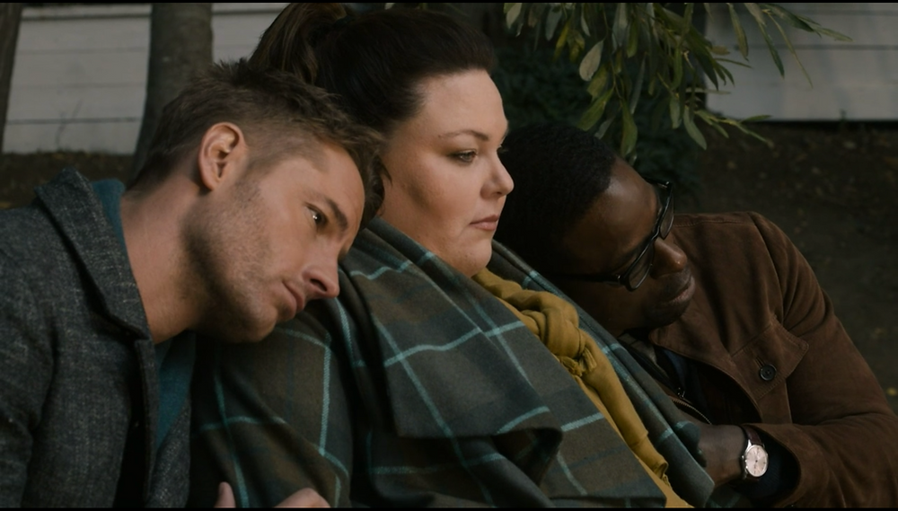 A still from This Is Us: The triplets hold each other, looking forelorn in grief.