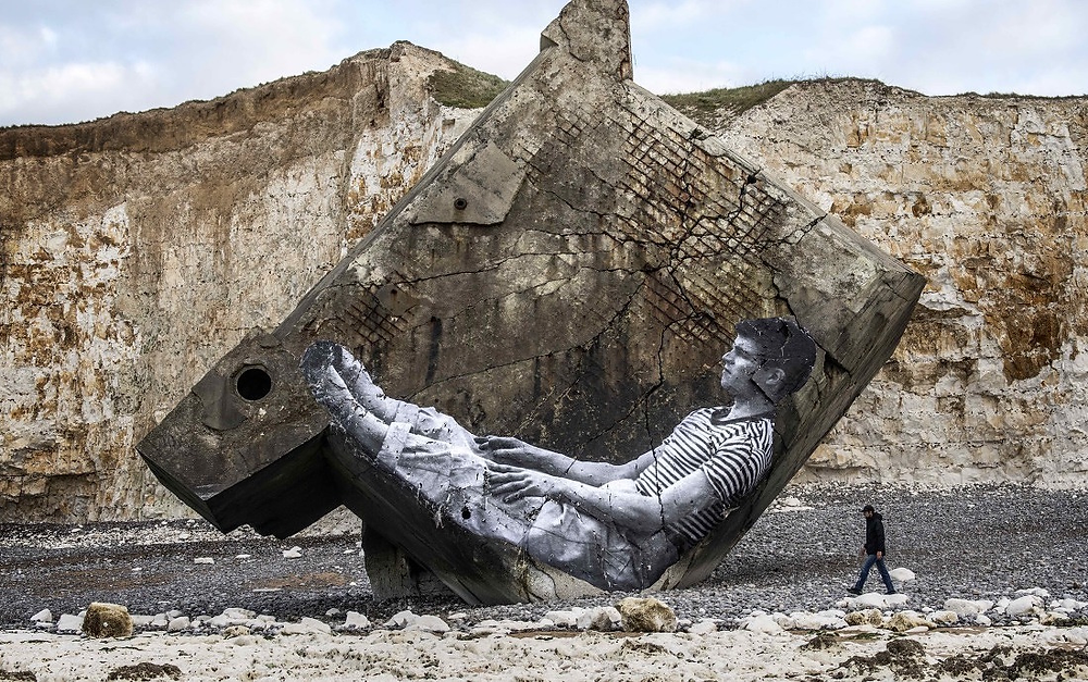 A still from Visages, Villages: The image of Bourdin sitting has been plastered, tilted somewhat, onto a fallen piece of large rock on a beach in Normandy.