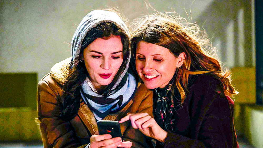 Aine and Shona from This Way Up are huddled up in warm outfits outdoors, both crouched over a phone and smiling at what's on screen