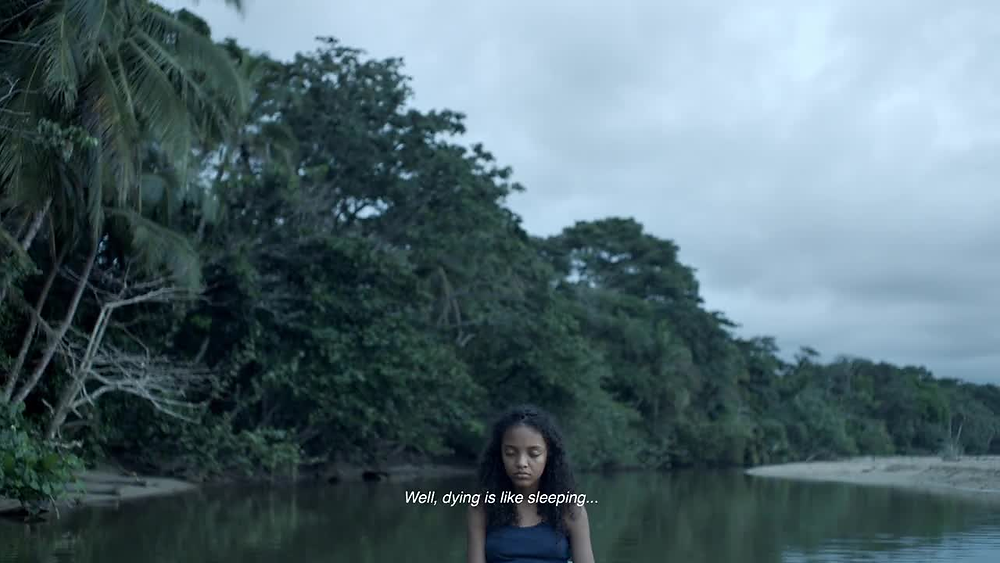 Selva, a young girl, is standing in a lake, only her upper torso can be seen in the centre of the shot. Behind her is a tropical forest.