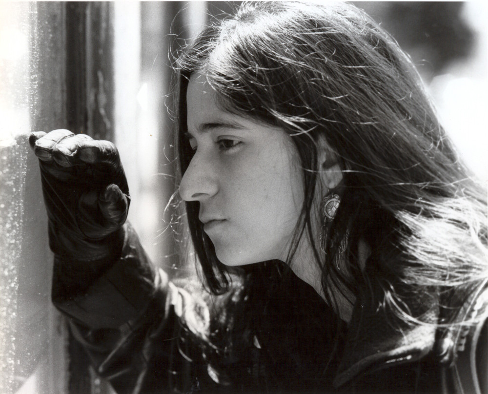 A still from Brincando el Charco: A young woman leans to a window to look through it wearing black leather gloves. The shot is in black and white.
