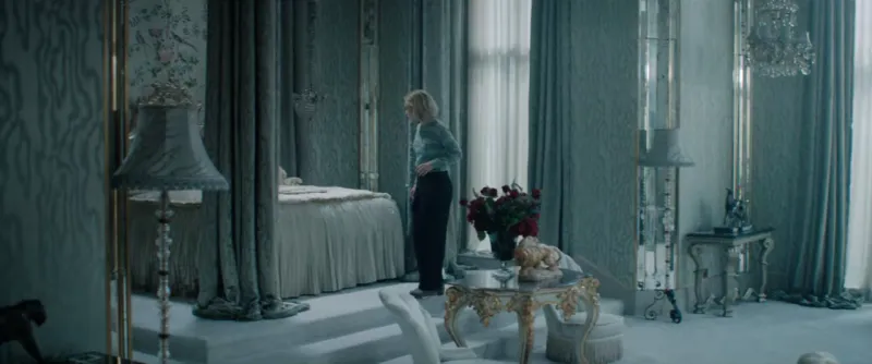 A frame from Wheatley's Rebecca: Mrs de Winter is standing in an expansive ornate bedroom, with furniture all in light blue tones.
