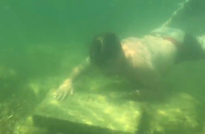 Pierre commémorative déposée au fond de l'eau.