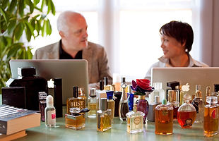 Luca Turin, Tania Sanchez with laptops at table covered in perfume bottles