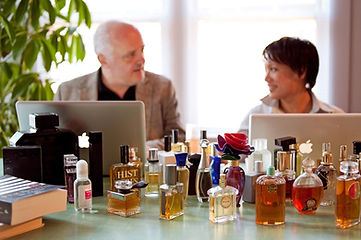 Luca Turin and Tania Sanchez, authors of Perfumes: the Guide, writing fragrance reviews with Apple laptops at a table full of perfume bottles