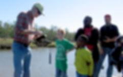 DCPG Creekwatcher volunteer demonstrates instrument to students
