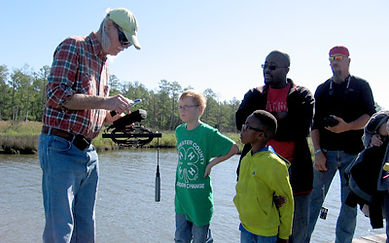 DCPG Creekwatcher volunteer demonstrates instrument to students