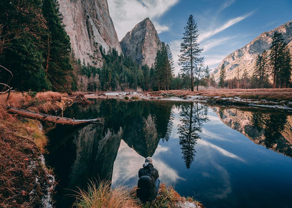 Traveler sitting around a lake amidst the mountains