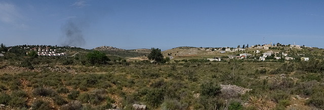 Panoramic view of Palestinian village and illegal Israeli settlement
