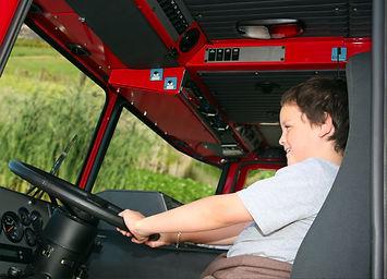 Young boy pretending to drive a fire tru