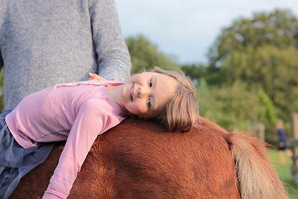 Mädchen liegt auf dem Rücken eines Ponys