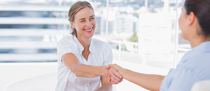 Two women shaking hands while smiling.