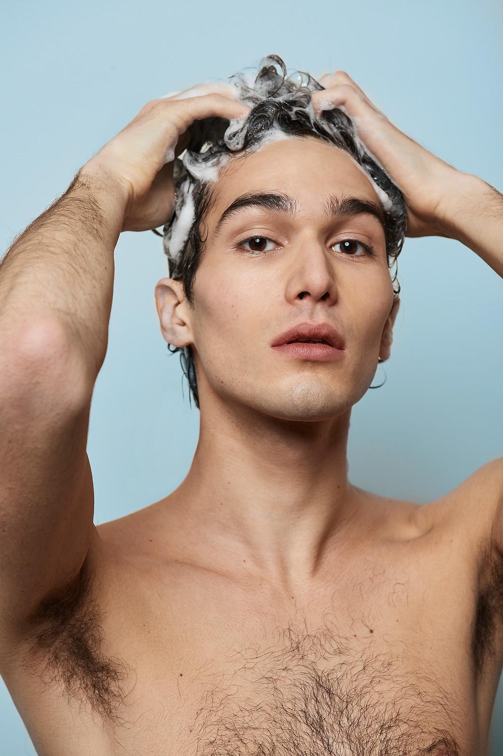Man shampooing hair in shower