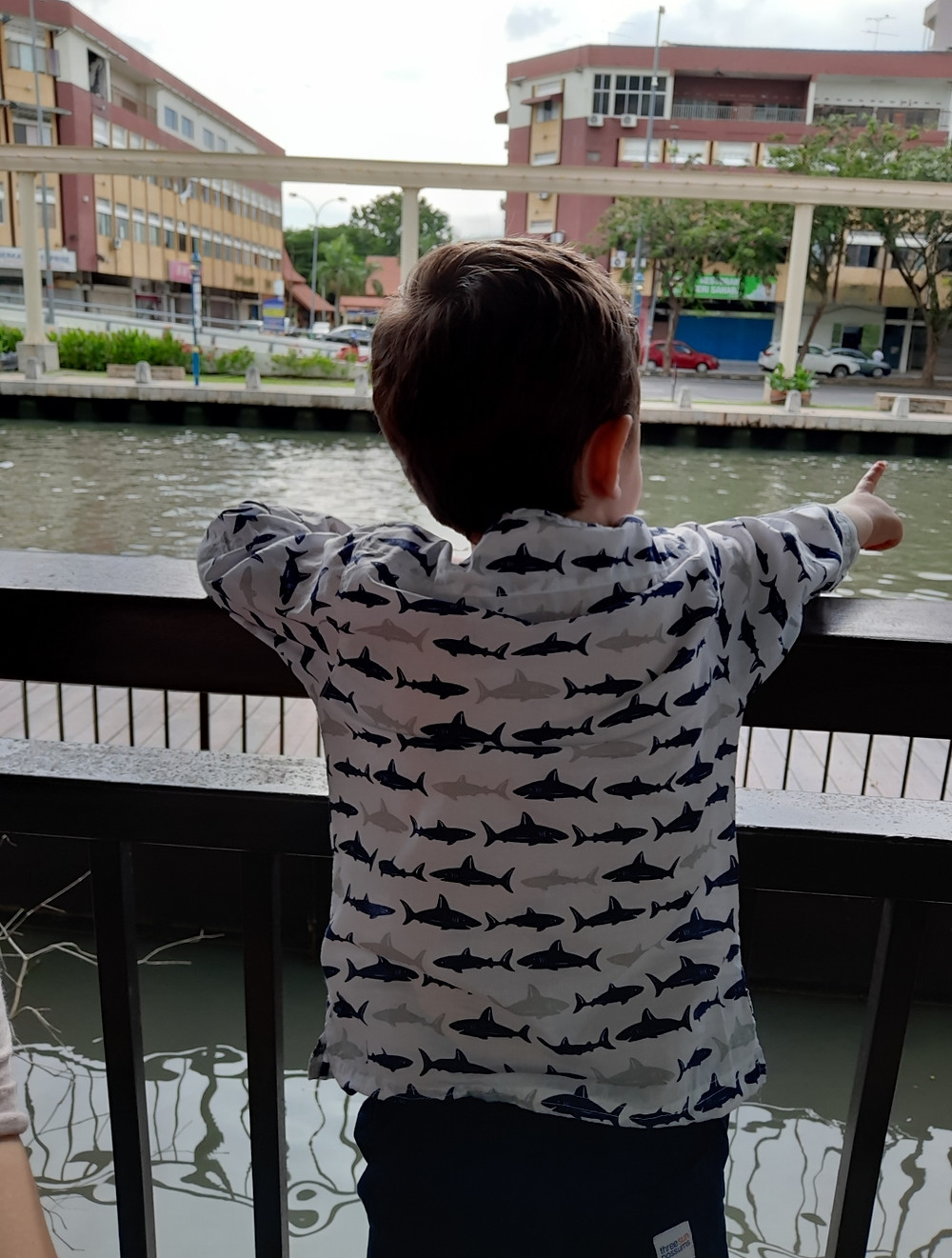 Popsicle top keeping him cool by river in Malaysia