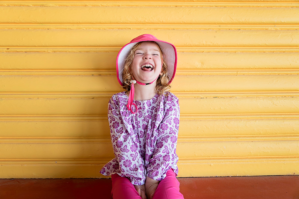 Girl laughing in sun top lightweight cotton and pants, wearing sunhat