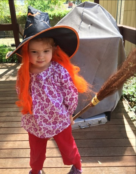 Halloween Witch wearing Lilac Breezy top and rainbow red Possum Pants with orange hair and broomstick